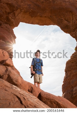 A Young Boy Stands in a Natural Arch and Looks Up in Wonder - stock photo