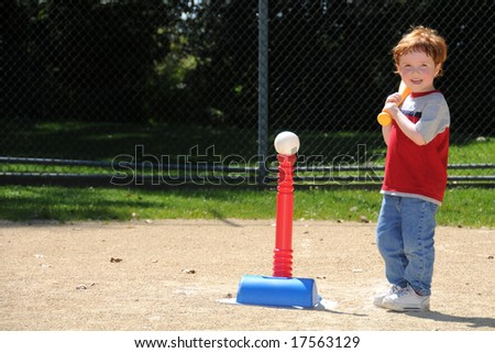 A young boy steps up to bat during t-ball practice at a neighborhood softball diamond. - stock photo