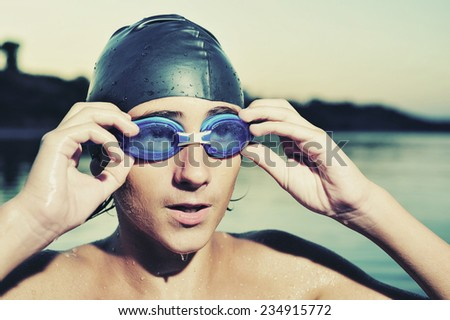 A young boy swimming in sea, close up  - stock photo