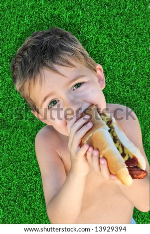 a young boy takes a bite of a hot dog - stock photo