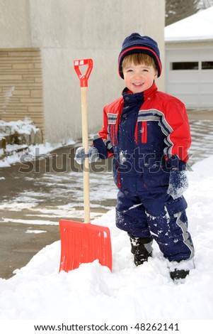 A young boy takes pride in completing a big shoveling job - stock photo