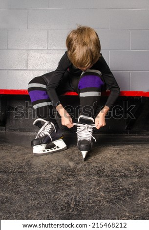 A Young Boy Ties His Hockey Skates in Rink Dressing Room - stock photo