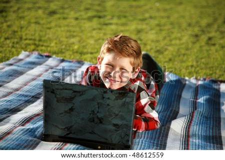 a young boy uses a laptop outside in the grass - stock photo