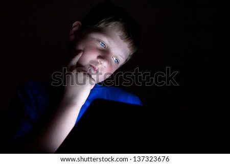 a young boy using an electronic tablet device looking puzzled. Light coming from the tablet. - stock photo