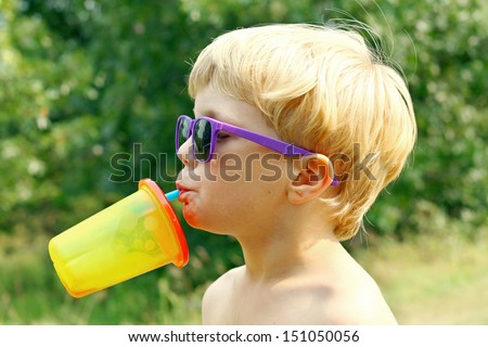 a young boy wearing purple sunglasses is tipping his head back drinking juice from a colorful sippy cup on a sunny summer day - stock photo