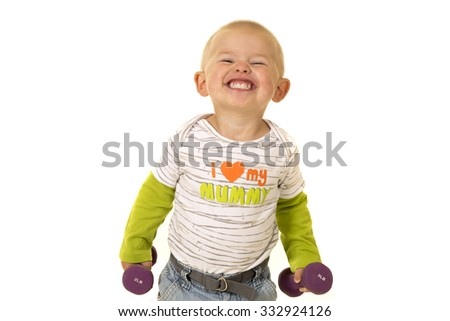 A young boy with a big smile, holding on to weights. - stock photo