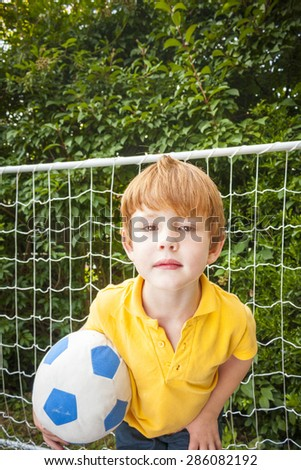 A young boy with a football standing in front of a goal looking into camera - stock photo
