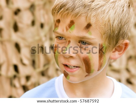 A young boy with camouflage paint on his face