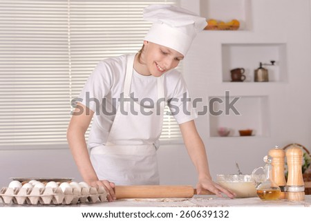 A young boy with dough prepares cookies