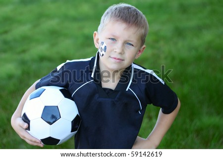 A young boy with painted face and soccer ball. - stock photo
