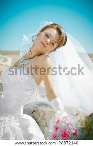 A young bride against an old stone wall holding a bouquet