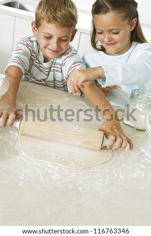 A young brother and sister enjoying themselves in the kitchen playing at being pastry chefs as they roll out the dough - stock photo