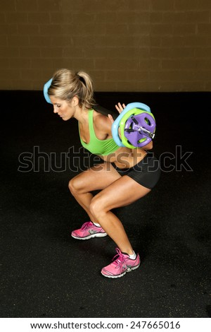 A young brunette doing a squat work out with a barbell in a gym. - stock photo