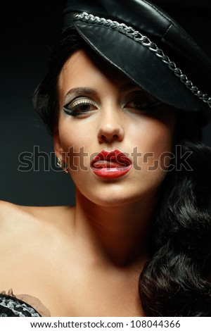 A young brunette lady mistress with bright red lips showing tongue - stock photo