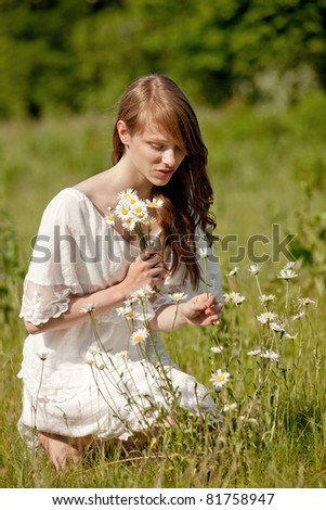 A young, brunette lady picks flowers on a summer meadow - stock photo