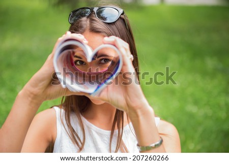 A young brunette woman outdoors in a park looking through a heart shaped magazine