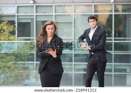 A young business couple standing in a modern buildings environment with a laptop computer - stock photo