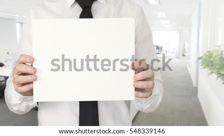 A young business man in the office with a tie holding an empty card with copy space.