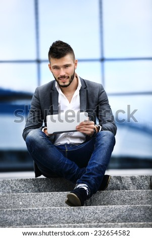 a young business man sitting on steps looking upset speaking on the phone with a laptop in front of him - stock photo