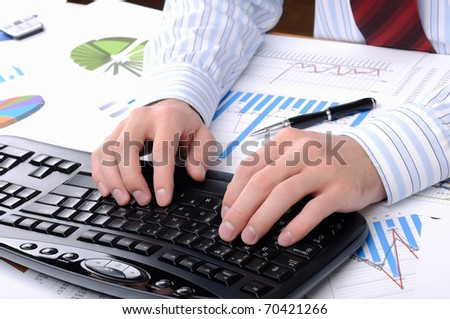 A young business man working in an office at his workplace. - stock photo
