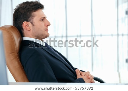 A young business manager is sitting relaxed in chair.