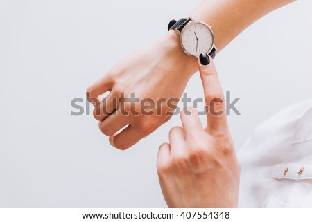 A young business woman is late on time, in a hurry she checks the deadline on her classic watch