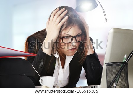 A young business woman is looking stressed as she works at her computer - stock photo