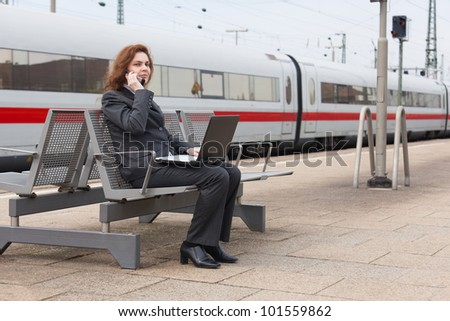 A young business woman is waiting for her train