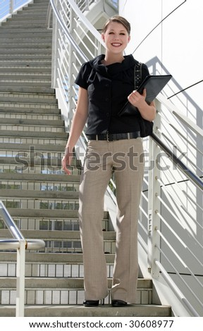 A young business woman standing on the stairs - stock photo