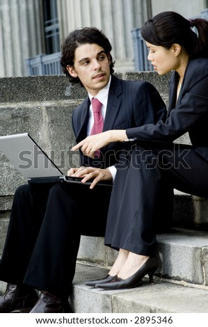 A young businessman and businesswoman discussing business with laptop computer on steps