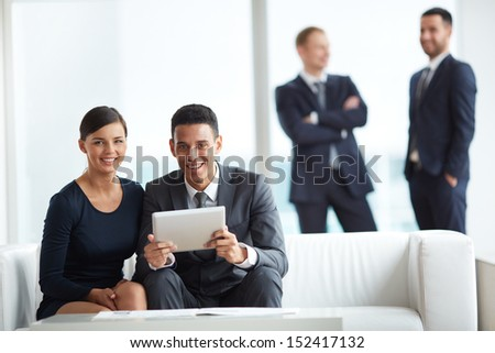 A young businessman and his colleague looking at camera while discussing data in notepad in working environment - stock photo