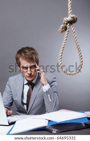 A young businessman behind a desk littered with documents, folders and look at the loop - stock photo