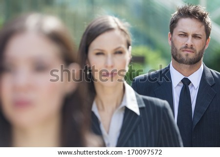 A young businessman business man with beard waiting behind two businesswomen in line
