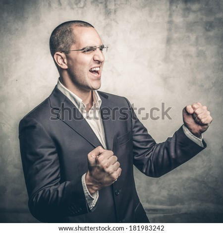 A young businessman gesturing in triumph - stock photo