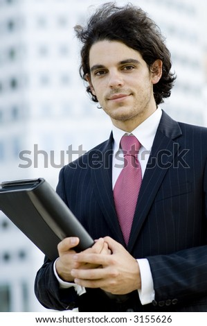 A young businessman holding a document folder standing outside with building behind (shallow depth of field used)