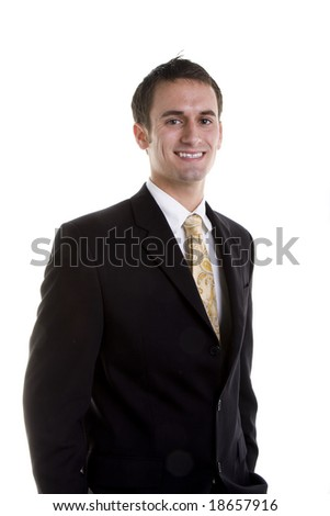 A young businessman in a suit smiling with hands in pockets