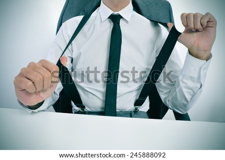 a young businessman in suspenders sitting at his office desk - stock photo