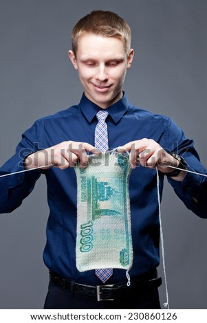 A young businessman is knitting thing, which look like as dollar banknote. - stock photo
