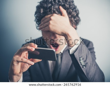 A young businessman is shocked by something on his smartphone - stock photo