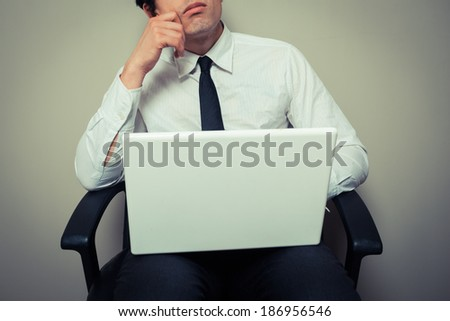 A young businessman is sitting in an office chair with his laptop and is thinking - stock photo