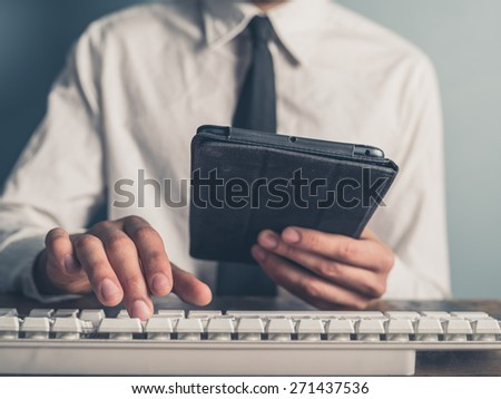 A young businessman is using a tablet and is typing on a keyboard - stock photo