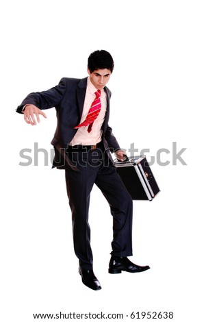 A young businessman is walking and holding a briefcase. - stock photo