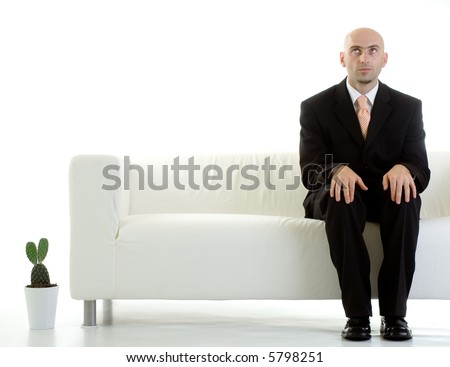 A young businessman looks upwards, waiting impatiently for his turn. - stock photo