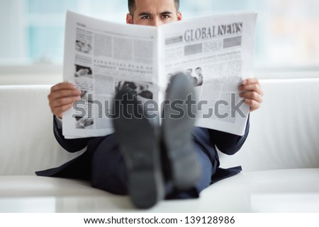 A young businessman on sofa looking at camera while reading newspaper