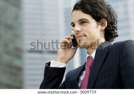 A young businessman on the phone outside in the city (shallow depth of field used)