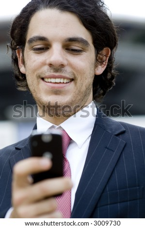 A young businessman outside using a phone to send text message