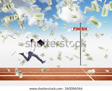 A young businessman running forward with a black folder in hand approaching the finish line, dollars falling from above. Blue sky at the background. Concept of competition. - stock photo