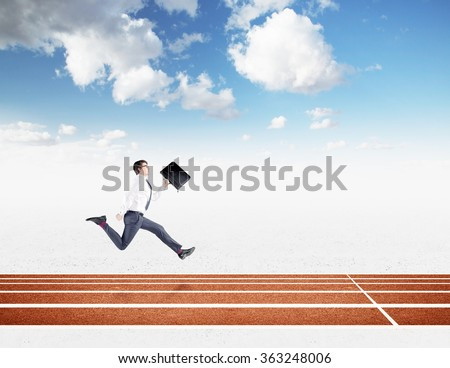 A young businessman running forward with a black folder in hand approaching the finish line. Blue sky at the background. Concept of competition. - stock photo
