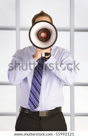 A Young businessman shouting into a megaphone.