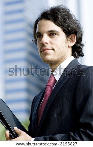 A young businessman standing outside in front of city skyscrapers